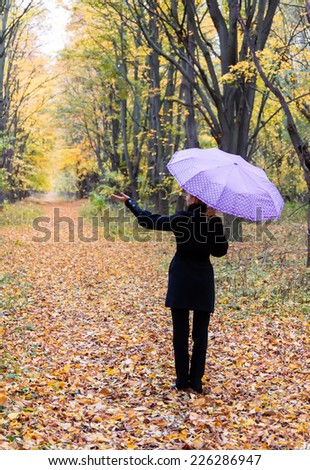 Young woman under a pink umbrella in autumn forest - stock photo