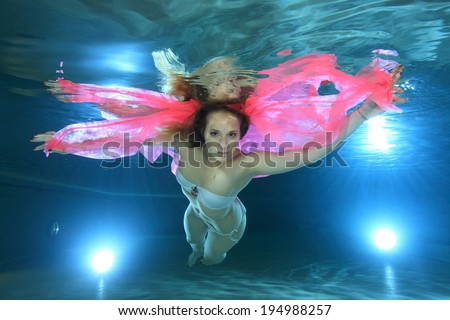 Young woman underwater in the pool floating with pink foulard - stock    Woman Floating Underwater