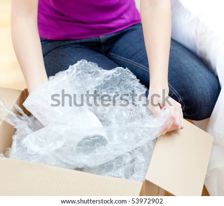 Young woman unpacking box in the living-room - stock photo