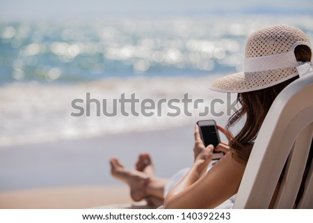 Young woman updating her social network status while relaxing at the beach - stock photo