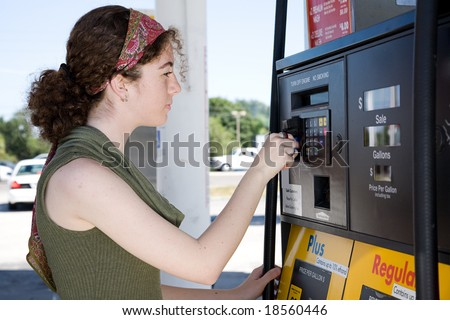 Young woman uses her credit card to pay for gasoline at the pump. - stock photo