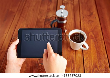 Young woman uses tablet while relaxing at home with coffee on the sofa couch - stock photo