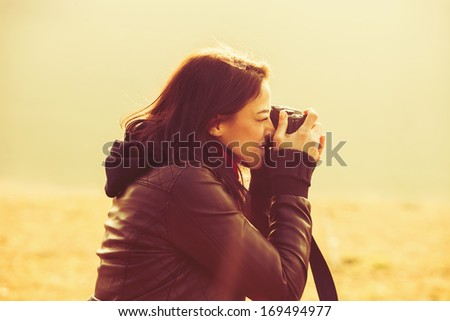 young woman using a camera to take photo outdoors retro colors - stock photo