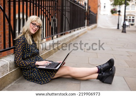 young woman using a computer in the street. - stock photo