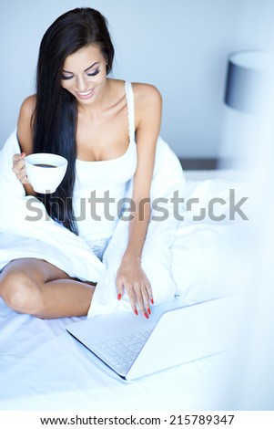 Young woman using a laptop in her bed sitting up with a white duvet draped around her drinking a cup of coffee and typing on the keyboard - stock photo