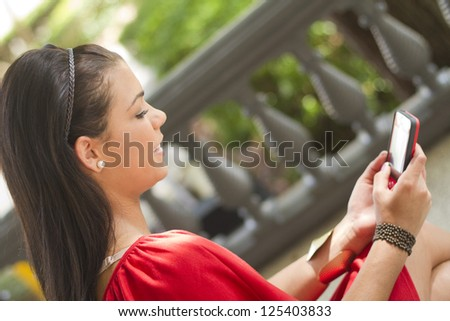 Young woman using a mobile phone outdoors - stock photo