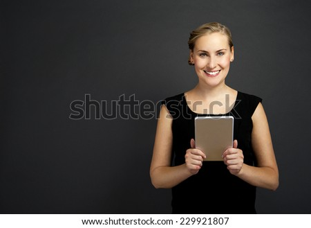 Young woman using a tablet over dark background  - stock photo