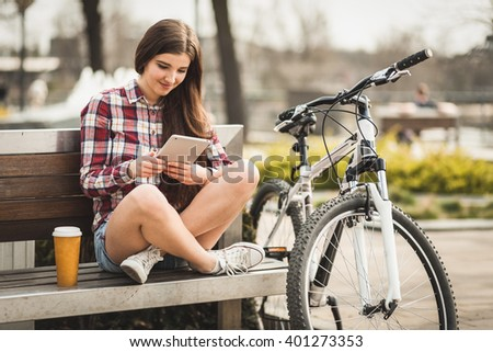 Young woman using a tablet pc in a park - stock photo