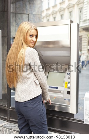 Young Woman using Bank ATM cash machine on the street - stock photo