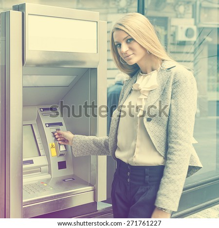 Young Woman using Bank ATM cashe machine on the street - stock photo