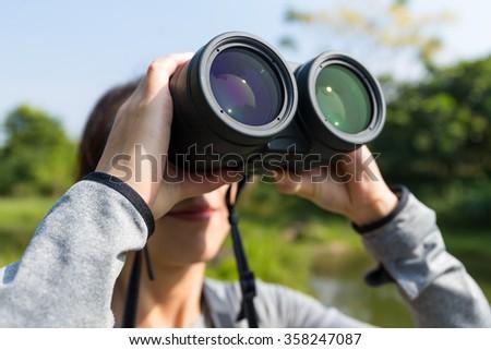 Young woman using binocular for bird watching - stock photo