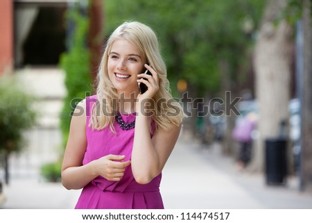 Young Woman using cell phone outdoors in city. - stock photo