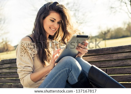 Young woman using digital tablet at the park - stock photo