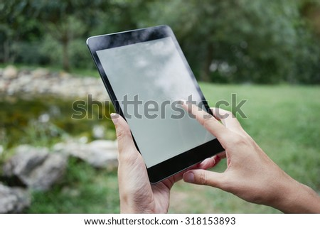 young woman using digital tablet in a park - stock photo