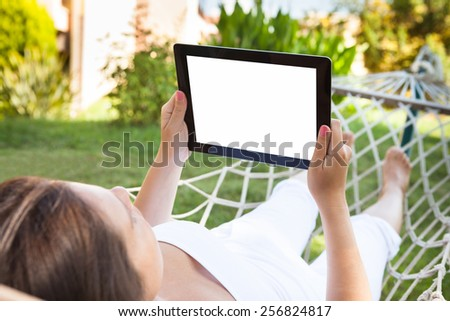 Young woman using digital tablet while lying in hammock at park - stock photo