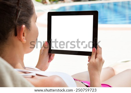 Young woman using digital tablet with blank screen at resort - stock photo