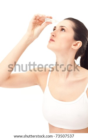 Young woman using eye drops, isolated on white background - stock photo