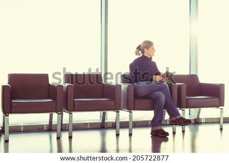 Young woman using her digital tablet pc at an airport lounge, modern waiting room, with backlight. - stock photo
