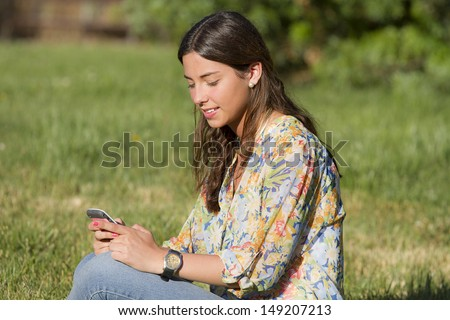 young woman using her mobile phone to chat and send messages in a park - stock photo
