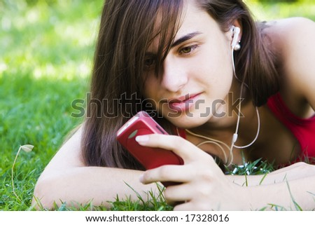 Young woman using her phone at the park. - stock photo