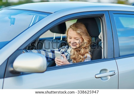 Young woman using her smartphone while driving a car - stock photo