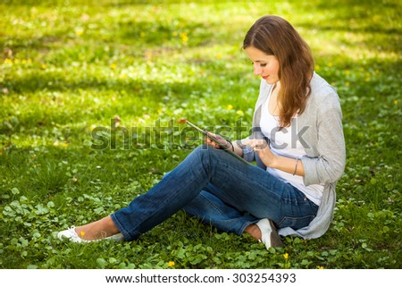 Young woman using her tablet computer while relaxing outdoors in a park on a lovely spring day - stock photo