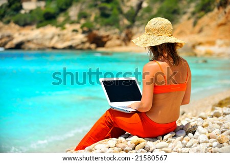 young woman using laptop by the sea - stock photo
