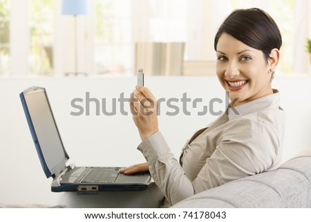 Young woman using laptop computer, showing up flash drive, smiling.? - stock photo