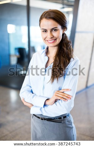 Young woman using laptop in front of conference room in office - stock photo