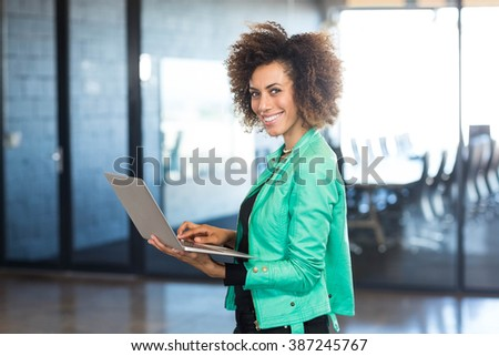 Young woman using laptop in front of conference room in the office - stock photo