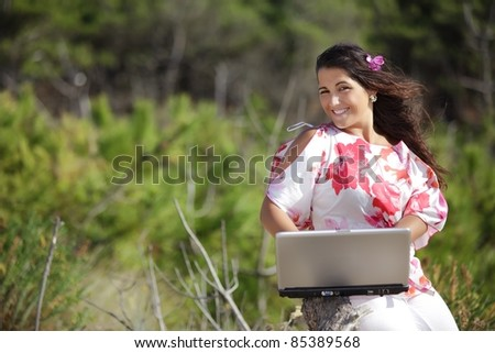 young woman using laptop in wild pine tree forest - stock photo