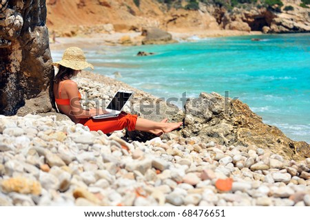 young woman using laptop on the beach - stock photo
