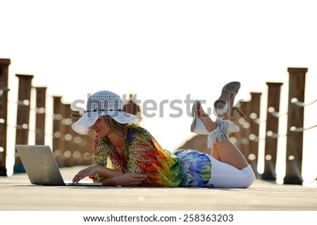 young woman using laptop outdoor in summer - stock photo