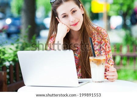Young woman using laptop outdoors  - stock photo