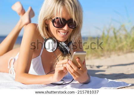 Young woman using mobile phone and wearing headphones on the beach - stock photo