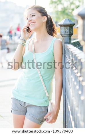 young woman using mobile phone outdoor - stock photo