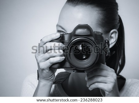 Young woman using professional camera - stock photo