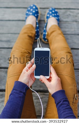 young woman using smart phone at wooden back - stock photo