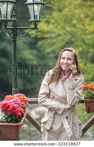 Young woman using smart phone - while standing on beautiful autumn background and mountain river. copy space - stock photo