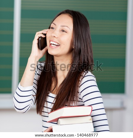 young woman using smartphone at classroom in university - stock photo