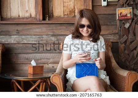 young woman using smartphone on cafe, wooden background - stock photo
