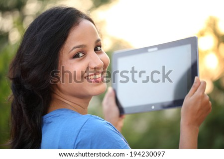 Young woman using tablet computer at outdoors - stock photo