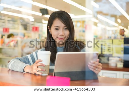 Young woman using tablet in coffee shop - stock photo