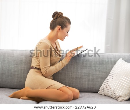 Young woman using tablet pc while sitting on sofa - stock photo