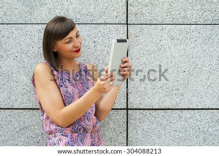 Young woman using tablet standing against the wall in the city smiling. - stock photo