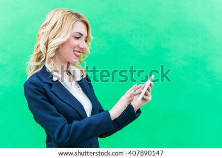 Young woman using tablet, standing. Wearing blue suit, she has blonde hair and blue or blue eyes, on a white background. Smile, always smiling. - stock photo