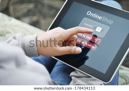 Young woman using touch screen device for online shopping - stock photo