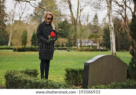 Young woman visiting a loved one at the cemetery paying respects with fresh rose flowers. Female grieving at graveyard. - stock photo