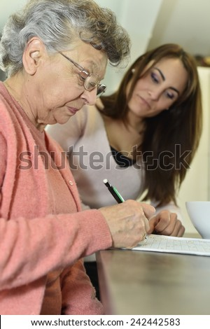 Young woman visiting elderly woman in nursing home - stock photo