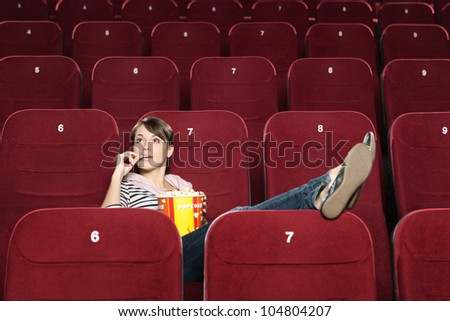 Young woman wait for a beginning of the movie - stock photo